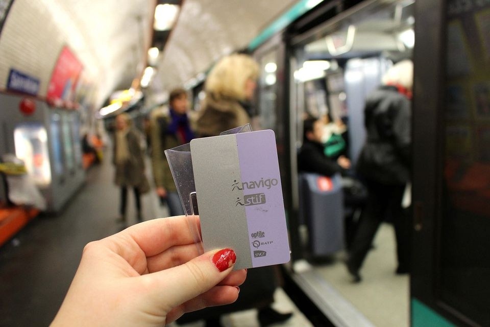 Navigo Pass card being held in a Paris Metro station