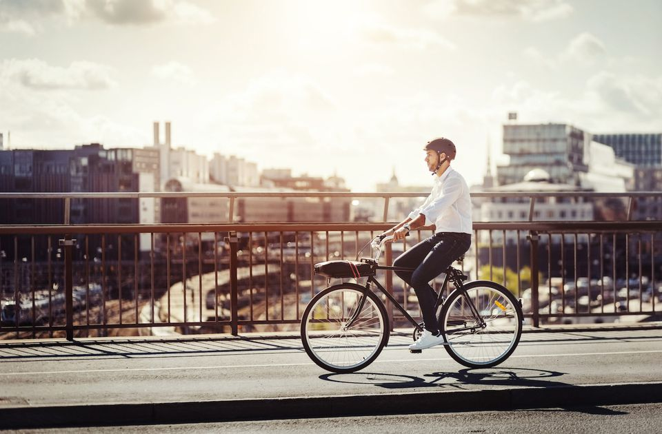 Man riding bicycle on bridge in city