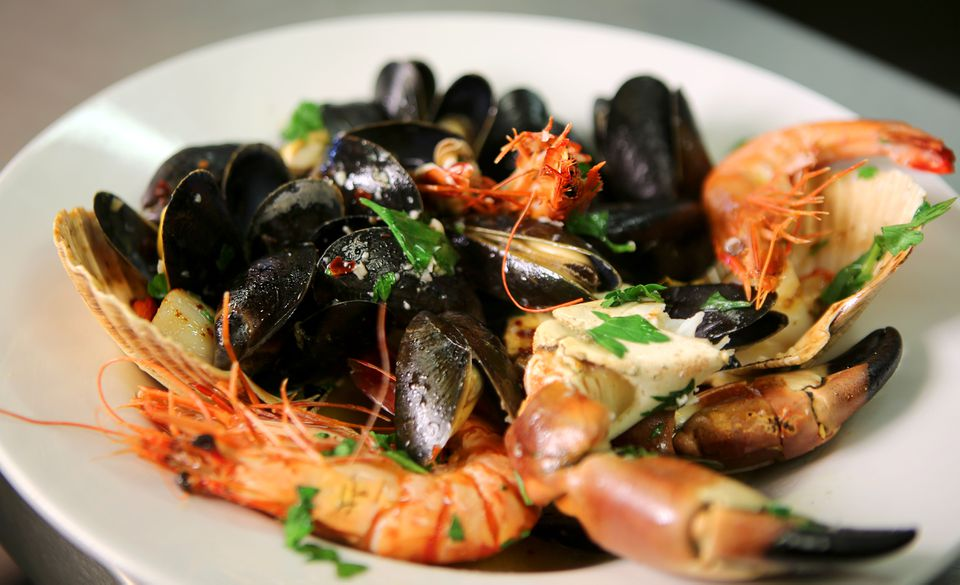 plate of mussels, head-on shrimp, crab, and scallops