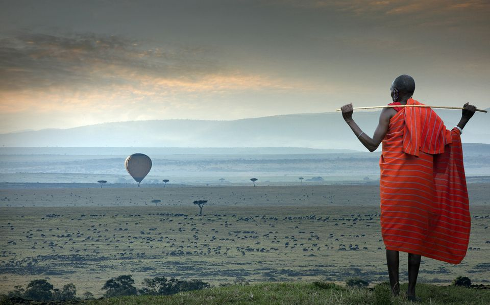 Masai man watching a hot-air balloon over the savannah