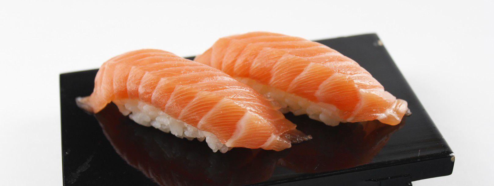 Close up of salmon nigiri on a square, black plate
