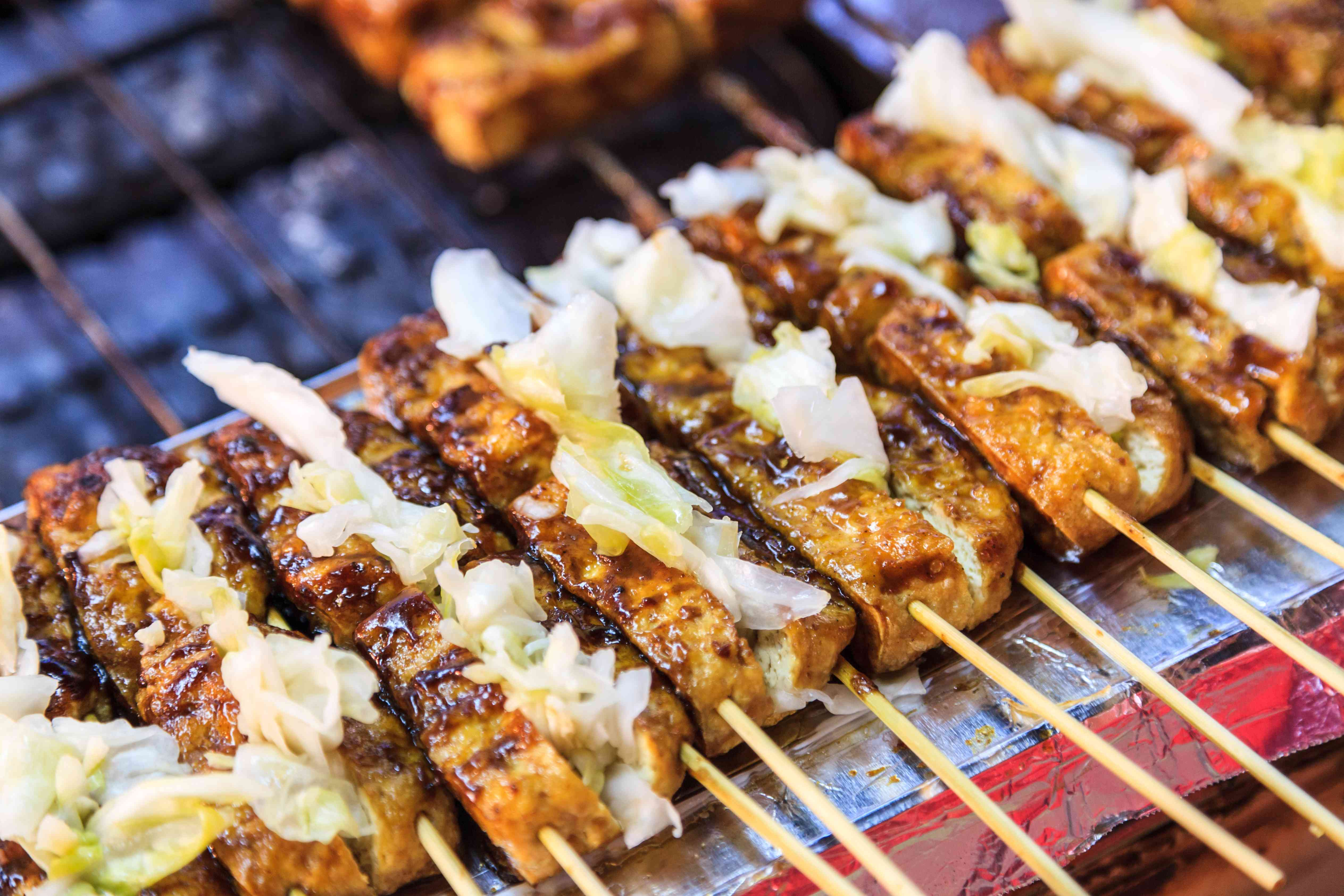 Barbecue stinky tofu on a grill at a night street market