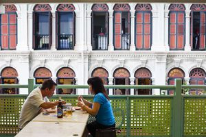 Singapore diners against a Chinatown Shophouse