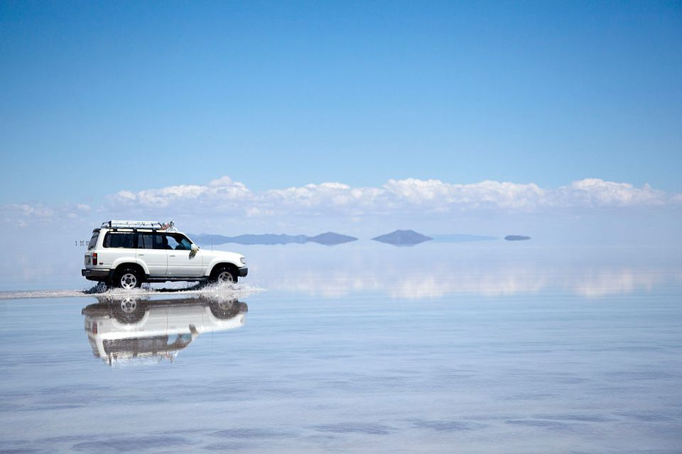 4x4 vehicle crossing salt flats in Bolivia