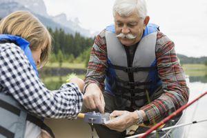 Older man and grandson fishing in lake