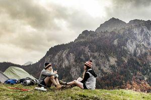 Young women camping beside mountains