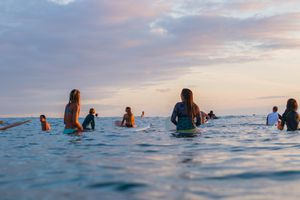 A group of people in the water on surfboards waiting for a waev
