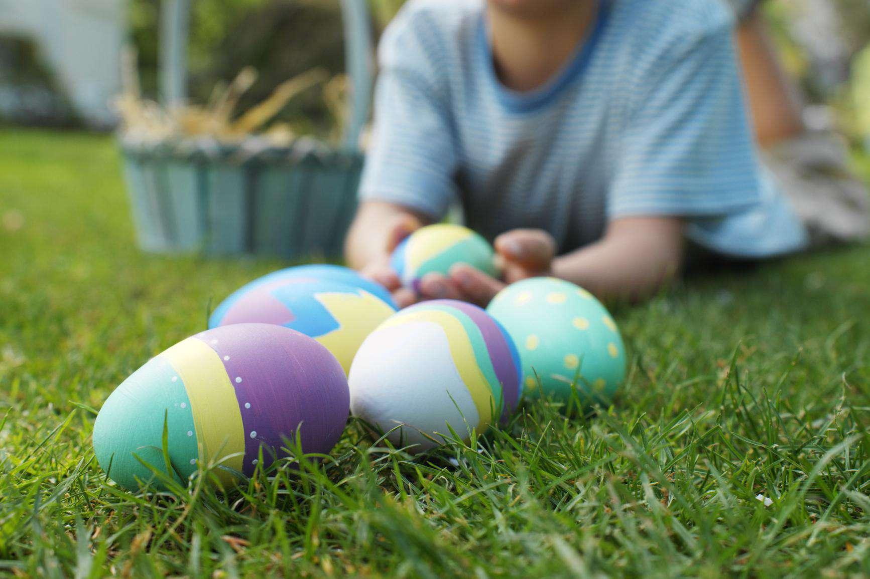 Niño (7-8) tumbado en el césped con huevos de Pascua