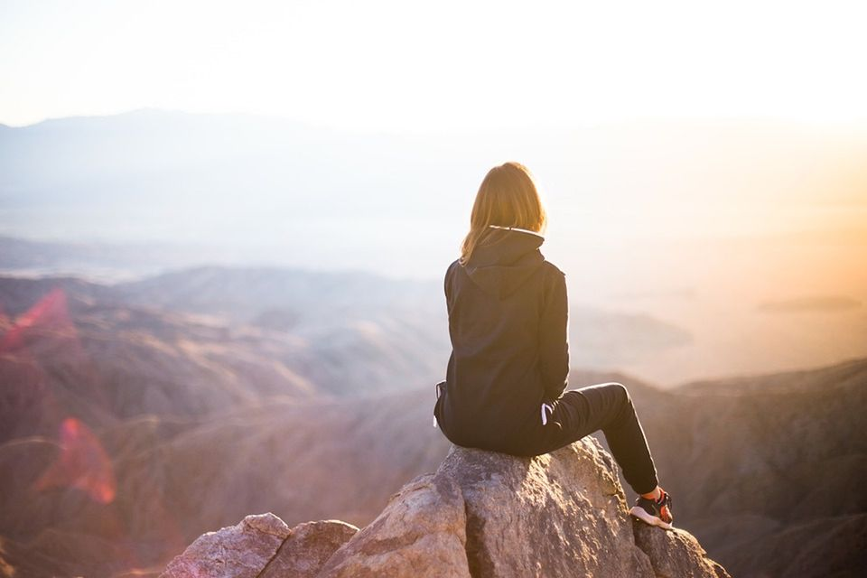 Woman sitting on rock overlooking mountains