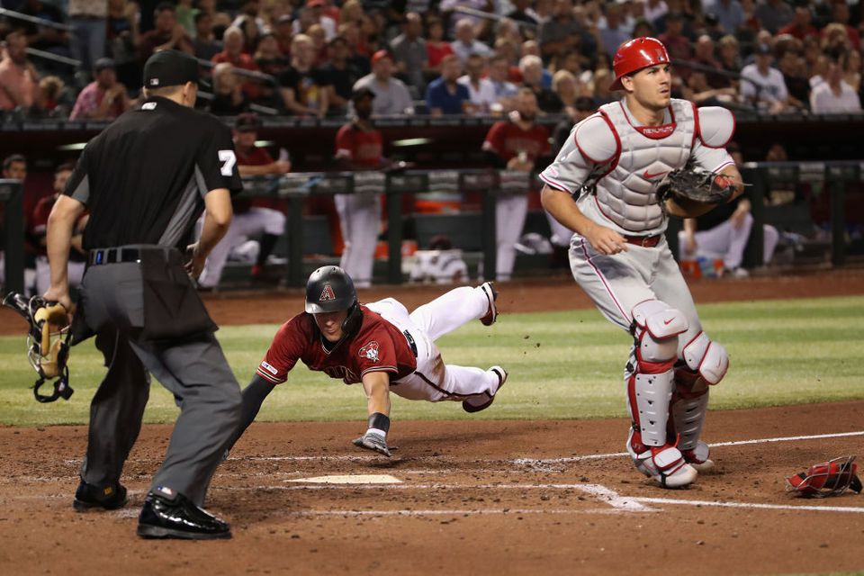 Nick Ahmed # 13 de los Diamondbacks de Arizona se sumerge en el plato para anotar una carrera
