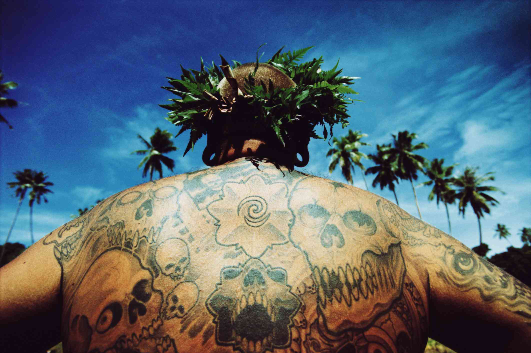 Tahitian man with body tattoo and fern crown on his head