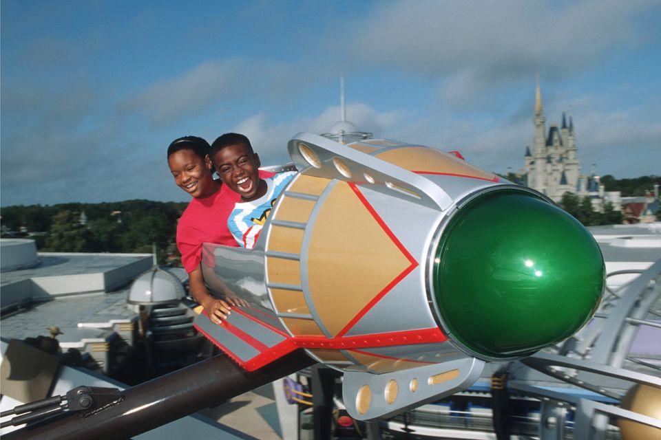 Los niños toman Astro Orbiter para dar una vuelta y disfrutan de la emoción del viaje.