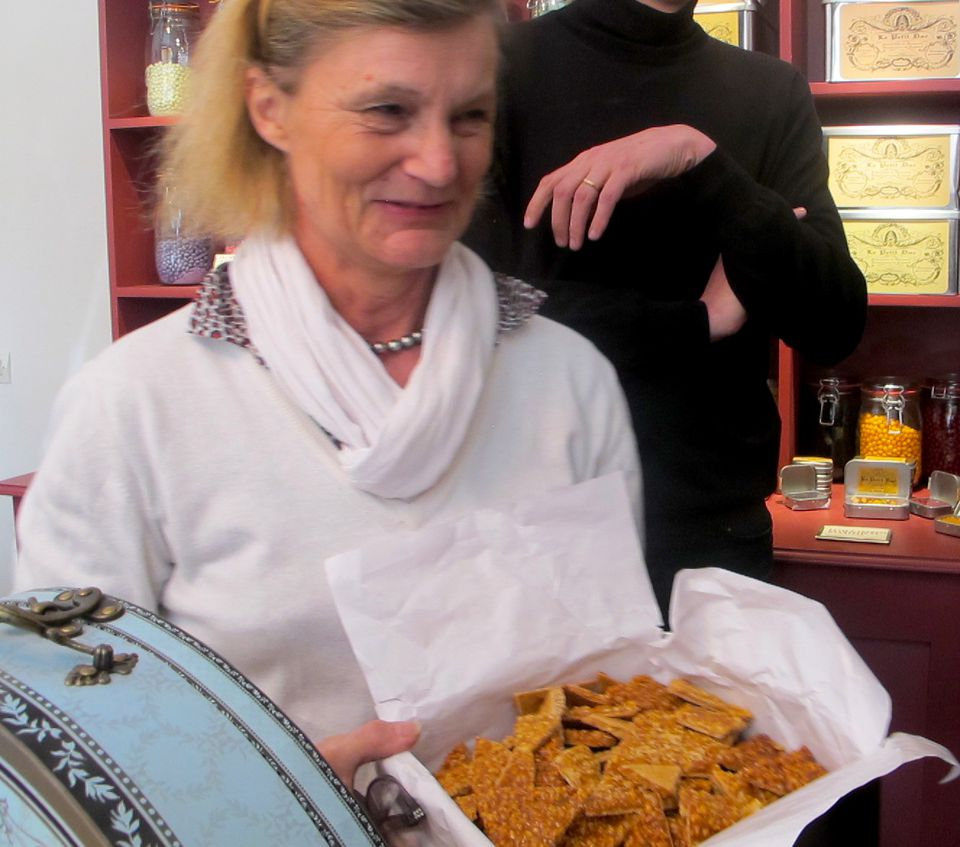 Christelle at Le Petit Duc artisan sweet shop in Paris, offering a special nut brittle as part of the Paris Tasting Passport Tour.