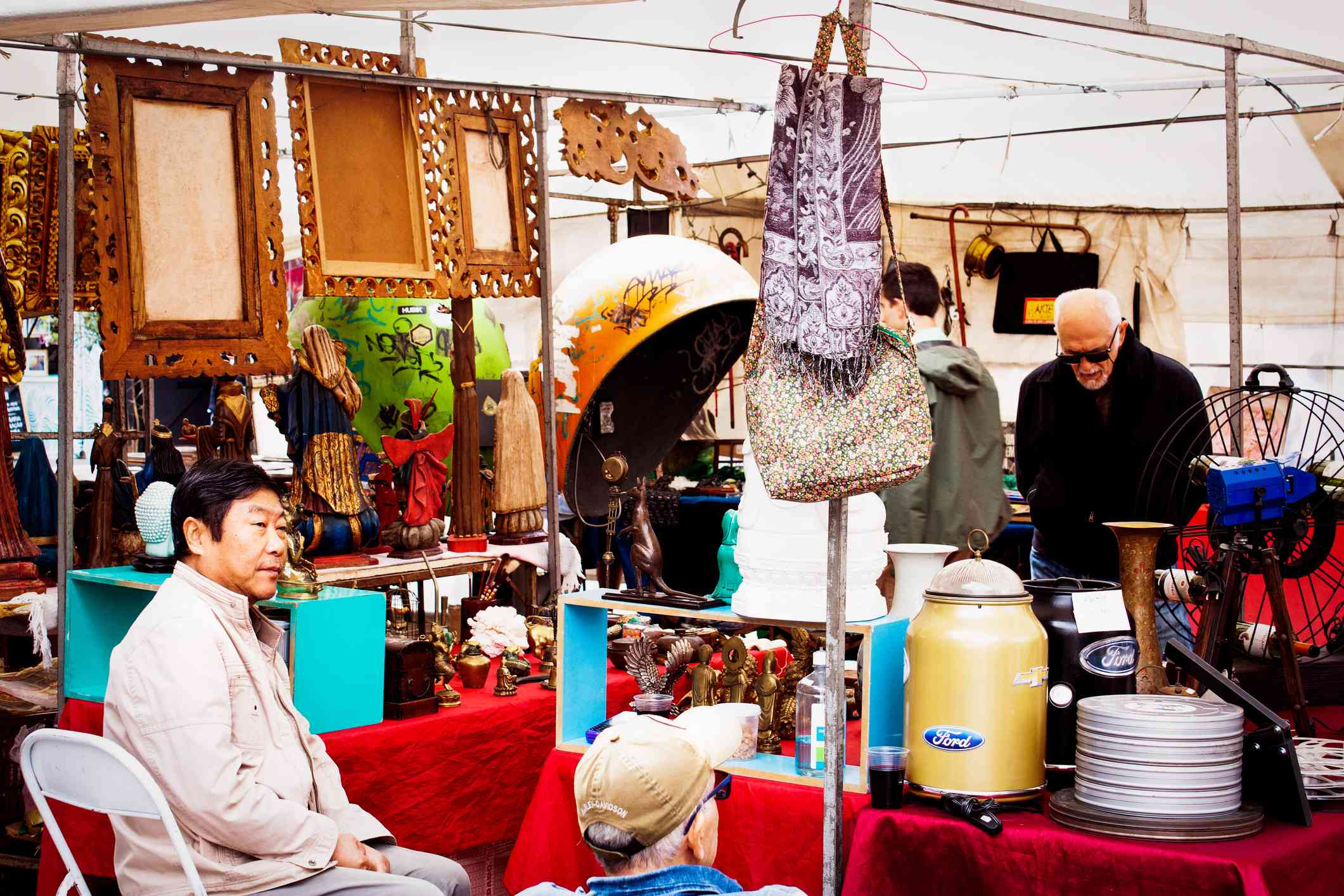 asian man sitting a chair next to an outdoor stall with a variety of objects for sale
