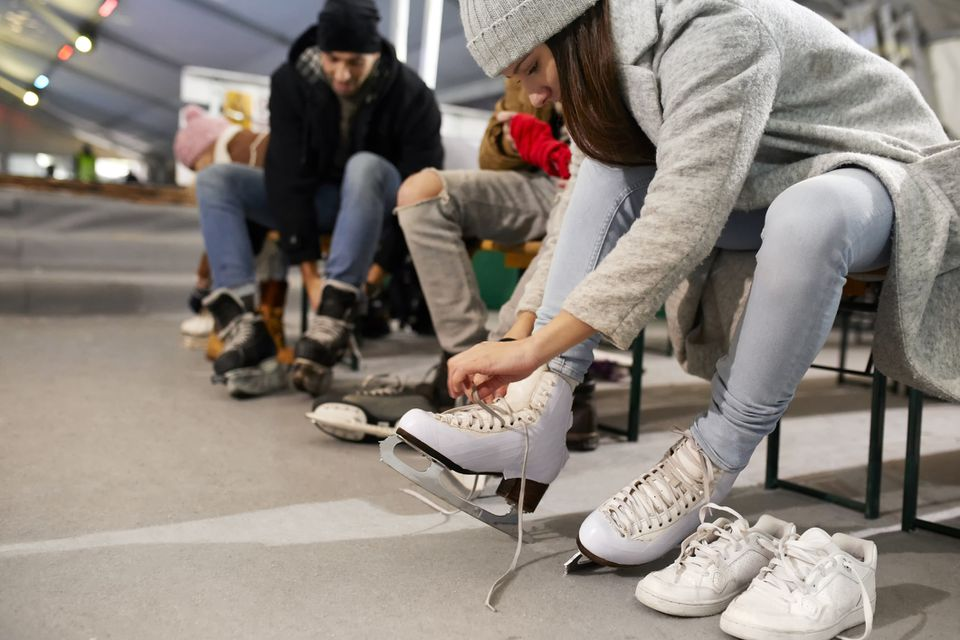 Friends putting on ice skates at an ice rink