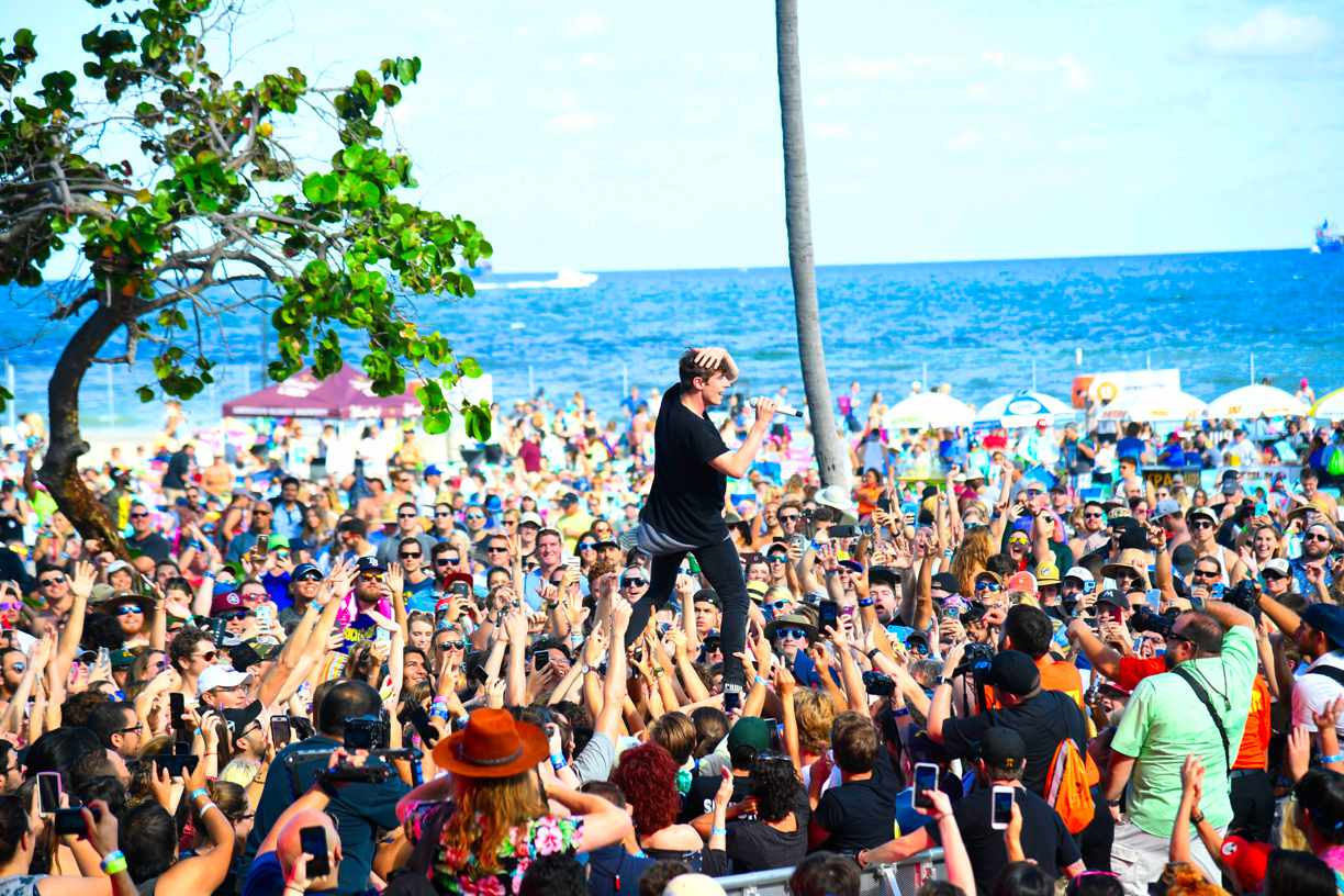 crowd of people at Riptide Music Festival with with a singer performing above them