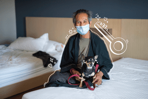 A man with his dog in a hotel room. With illustrated key and icons around them