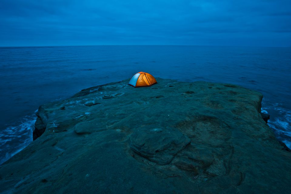 An illuminated tent sits on cliff overlooking the Pacific Ocean in San Diego, C
