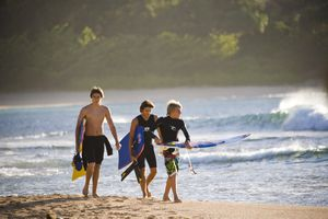 three male surfers walking on the beach