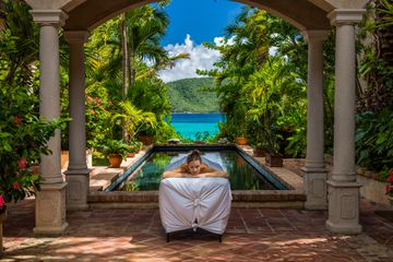 woman waiting for a massage on a table at a beautiful villa in Caribbean
