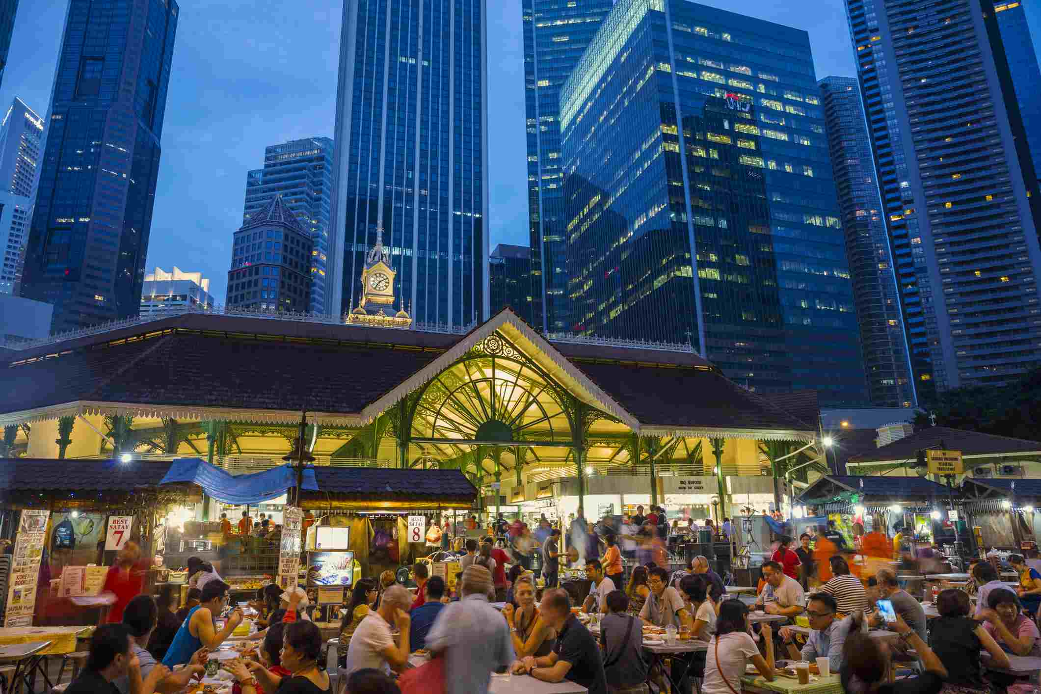 people eating outside on picnic tables at a hawker center at night