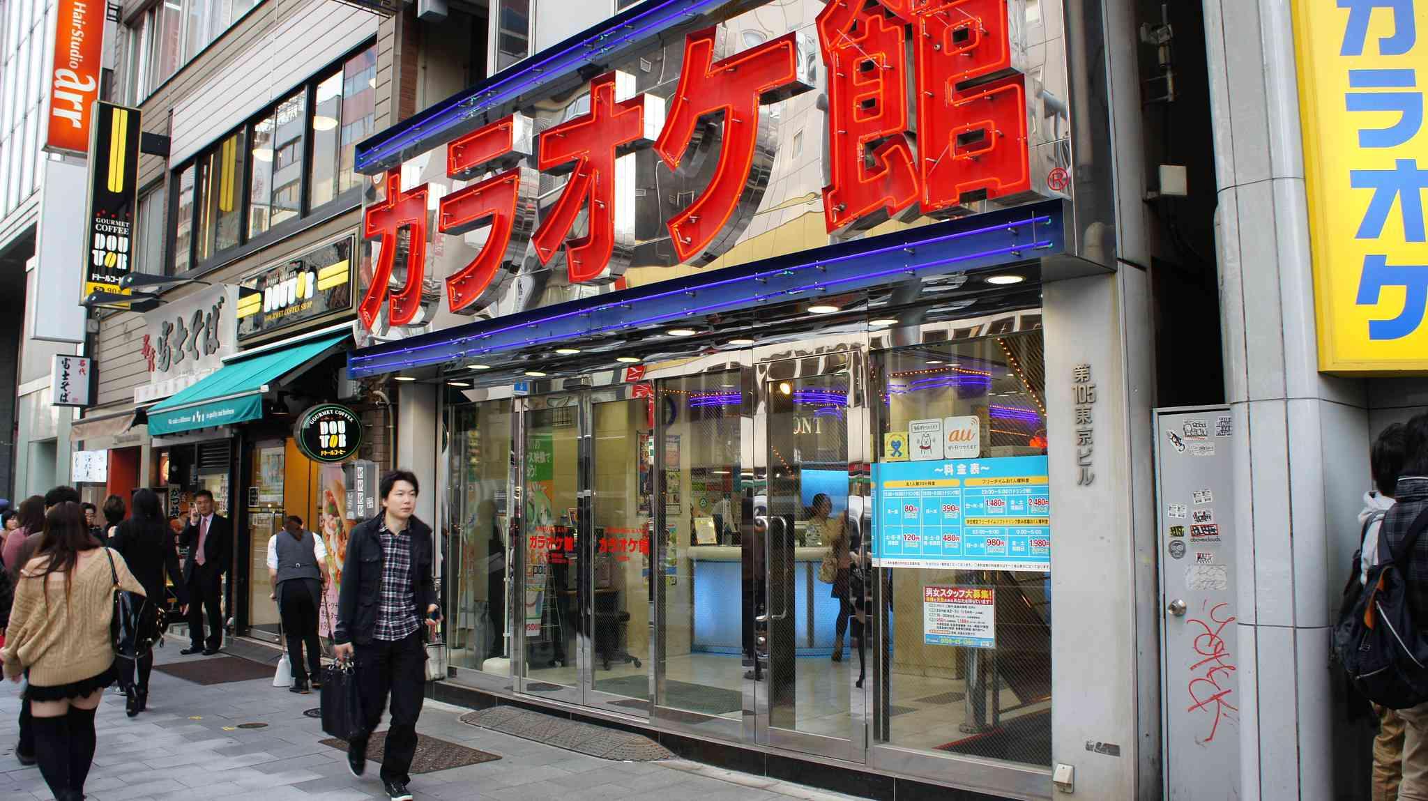 Outside of the Shibuya Karaoke Kan, with people walking around