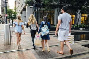 Friends crossing street in Houston carrying shopping bags