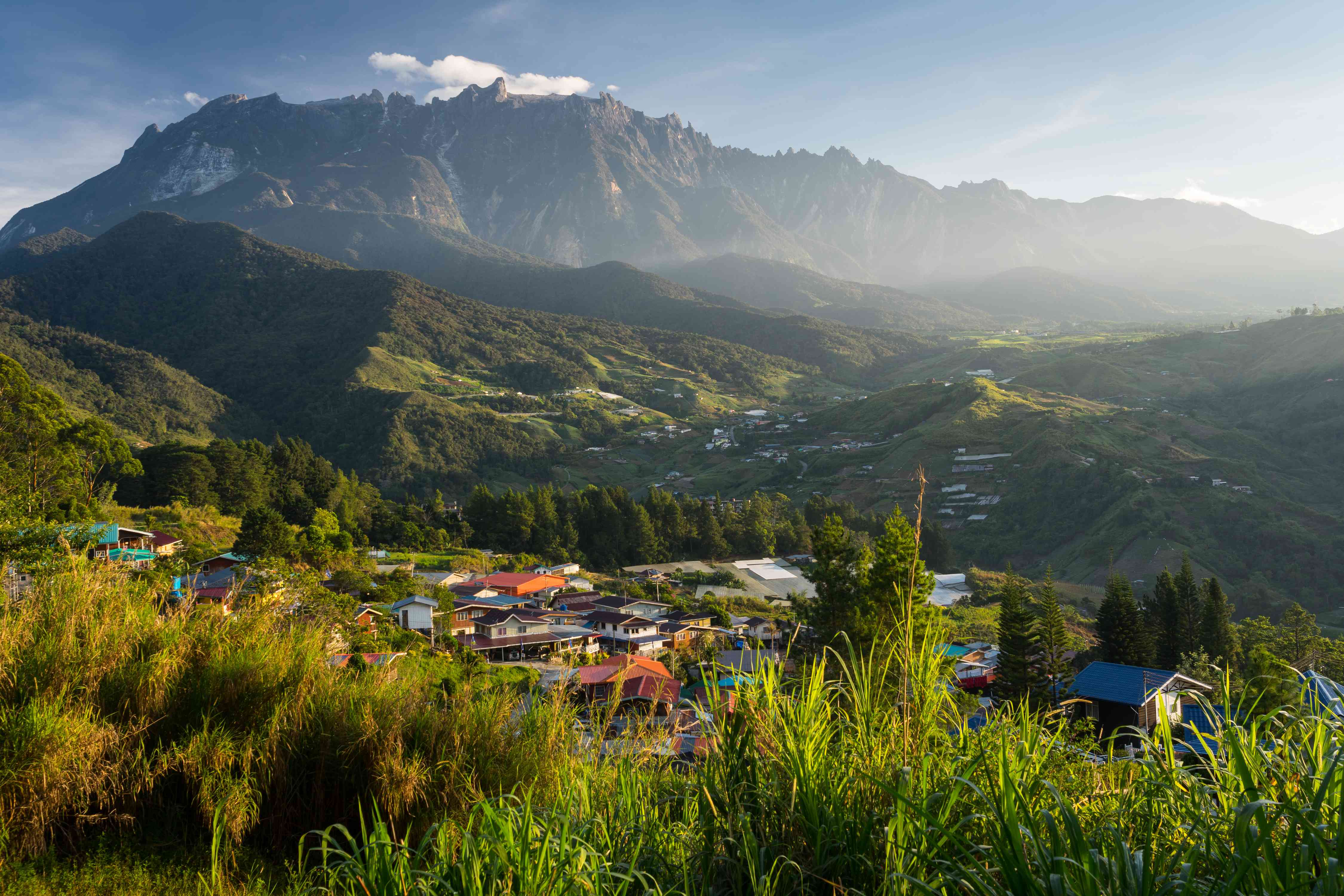 Mount Kinabalu stands about a village in Sabah, Borneo