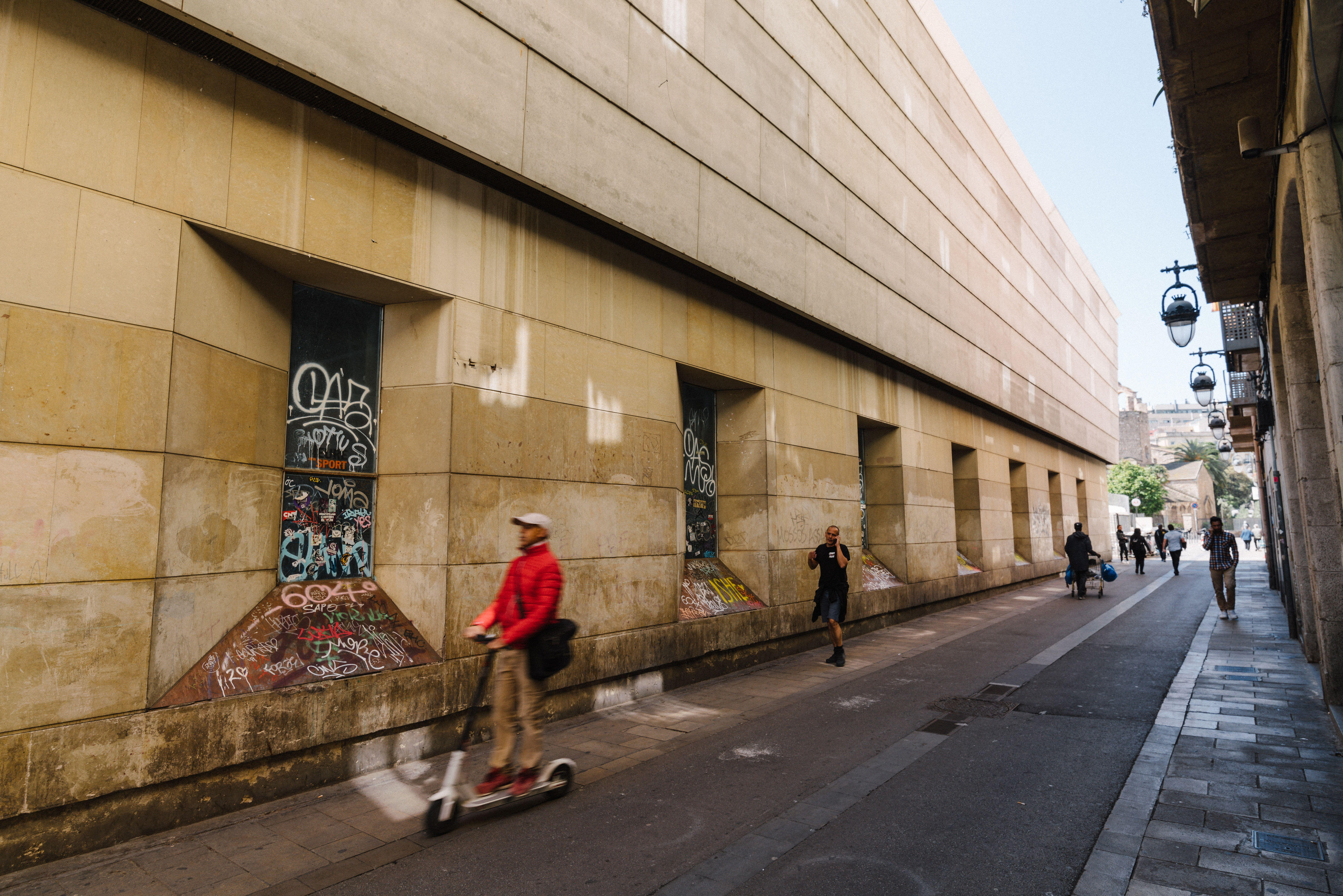 Pedestrians going past street art in an alley