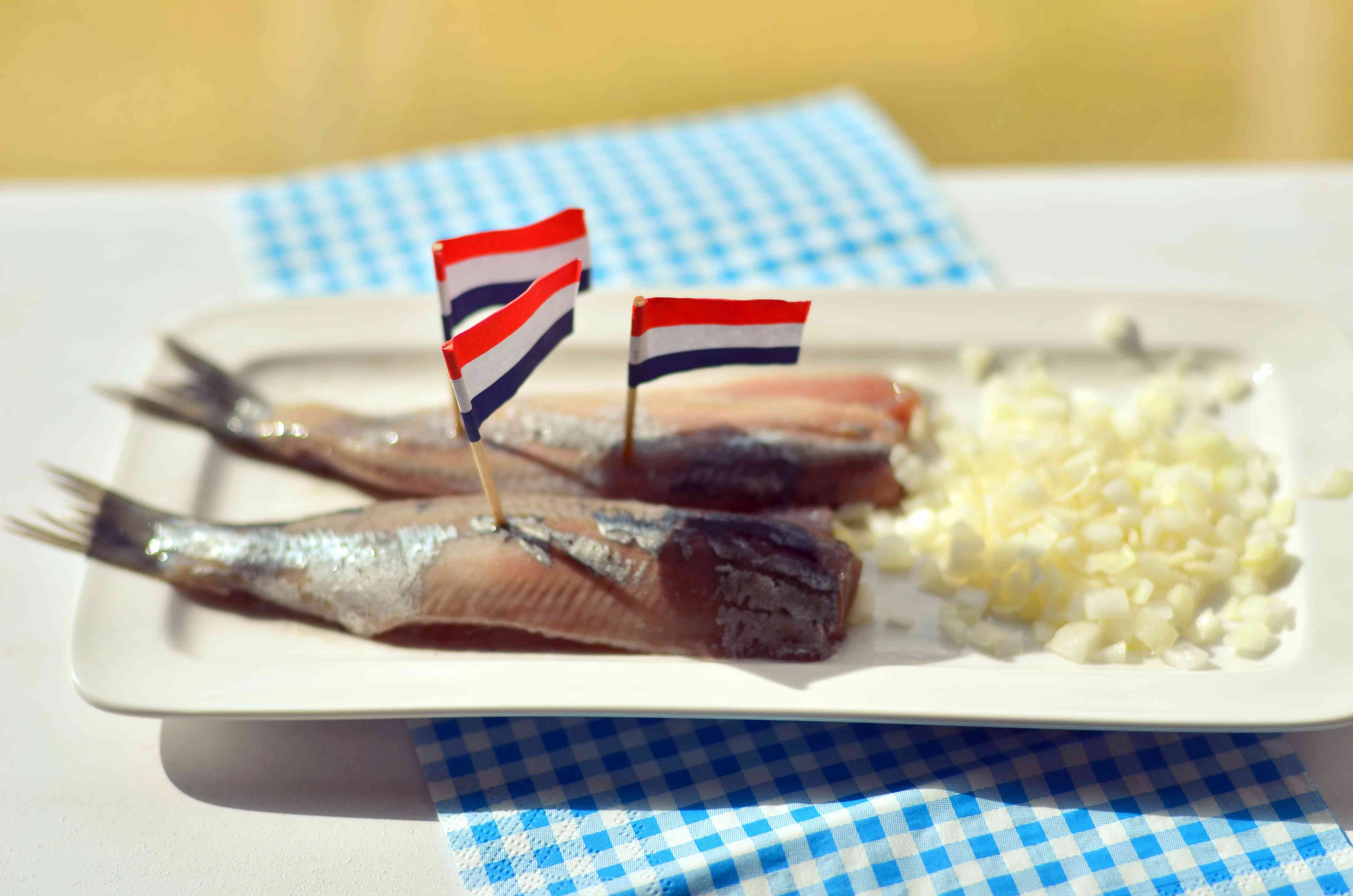 two halves of raw, fresh herring on a plate with diced onion. The herring closer to the camera has one dutch flag toothpick in it and the herring farther away has two dutch flag toothpicks