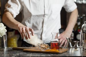 Bartender uncovering a block of ice on a cutting board