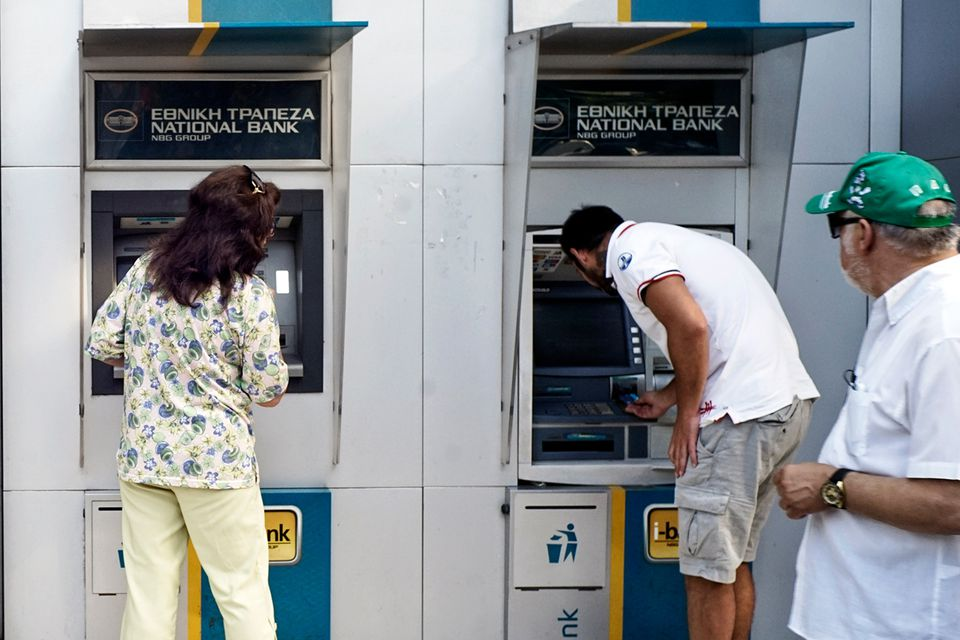 People using ATM machines in Greece