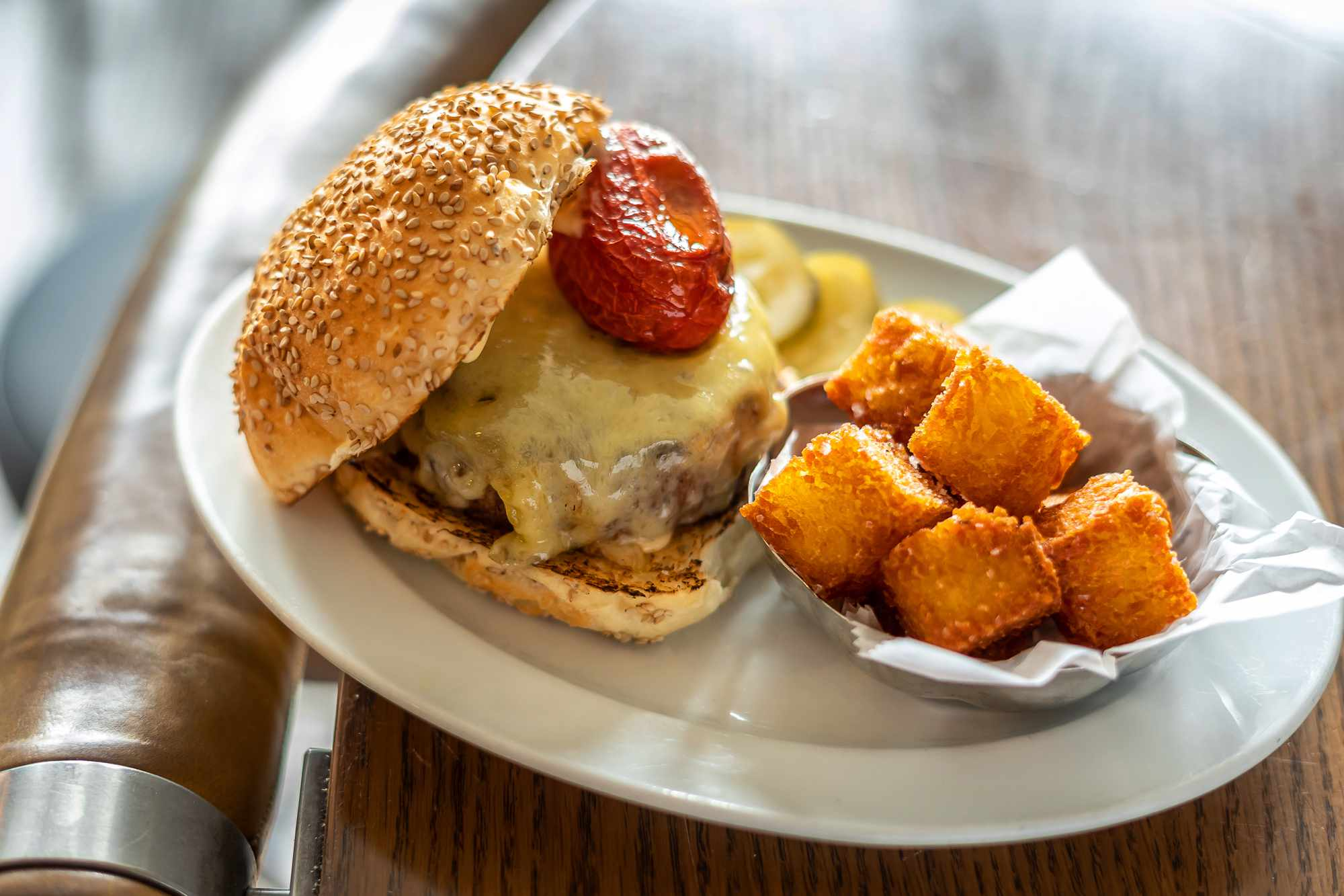 Cheese burger from the loyal with a whole roasted cherry tomato