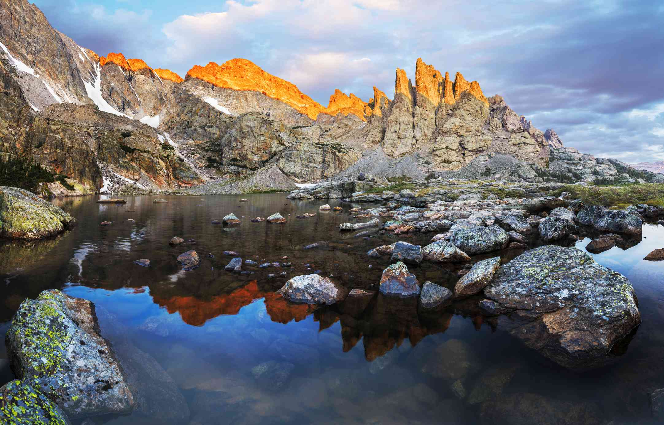 Photograph capturing Alpenglow on the sharks teeth above Rocky Mountain National Park Sky Pond