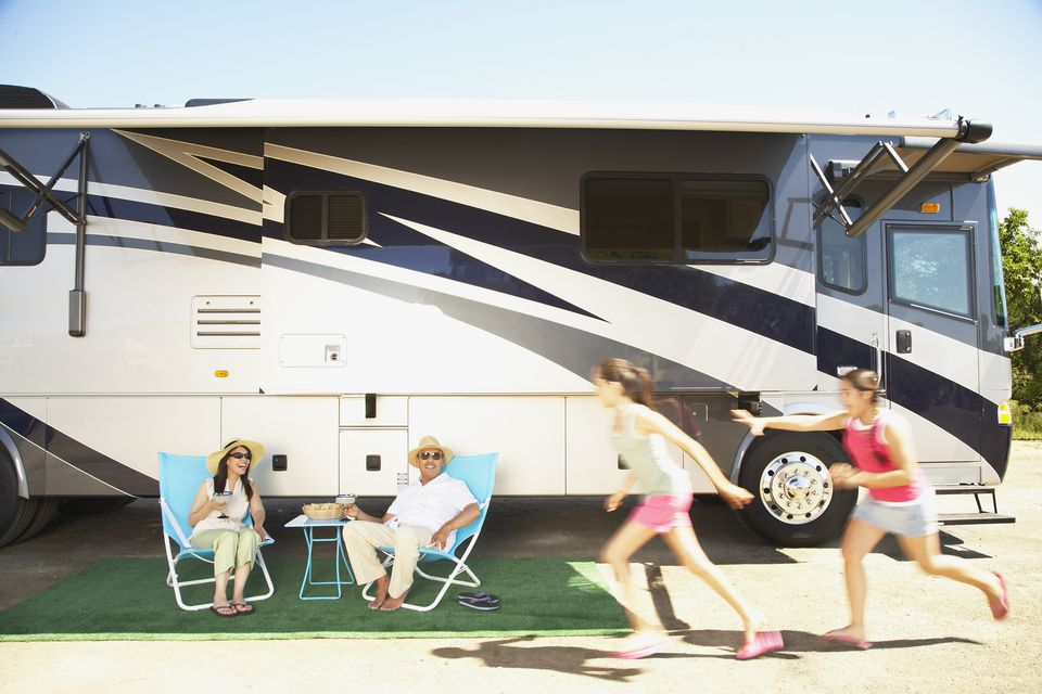 family relaxing next to RV