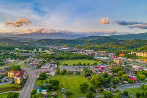 Aerial picture of the town of Pigeon Forge. There are assorted houses, plenty of greed fields with tree-covered mountains in the background