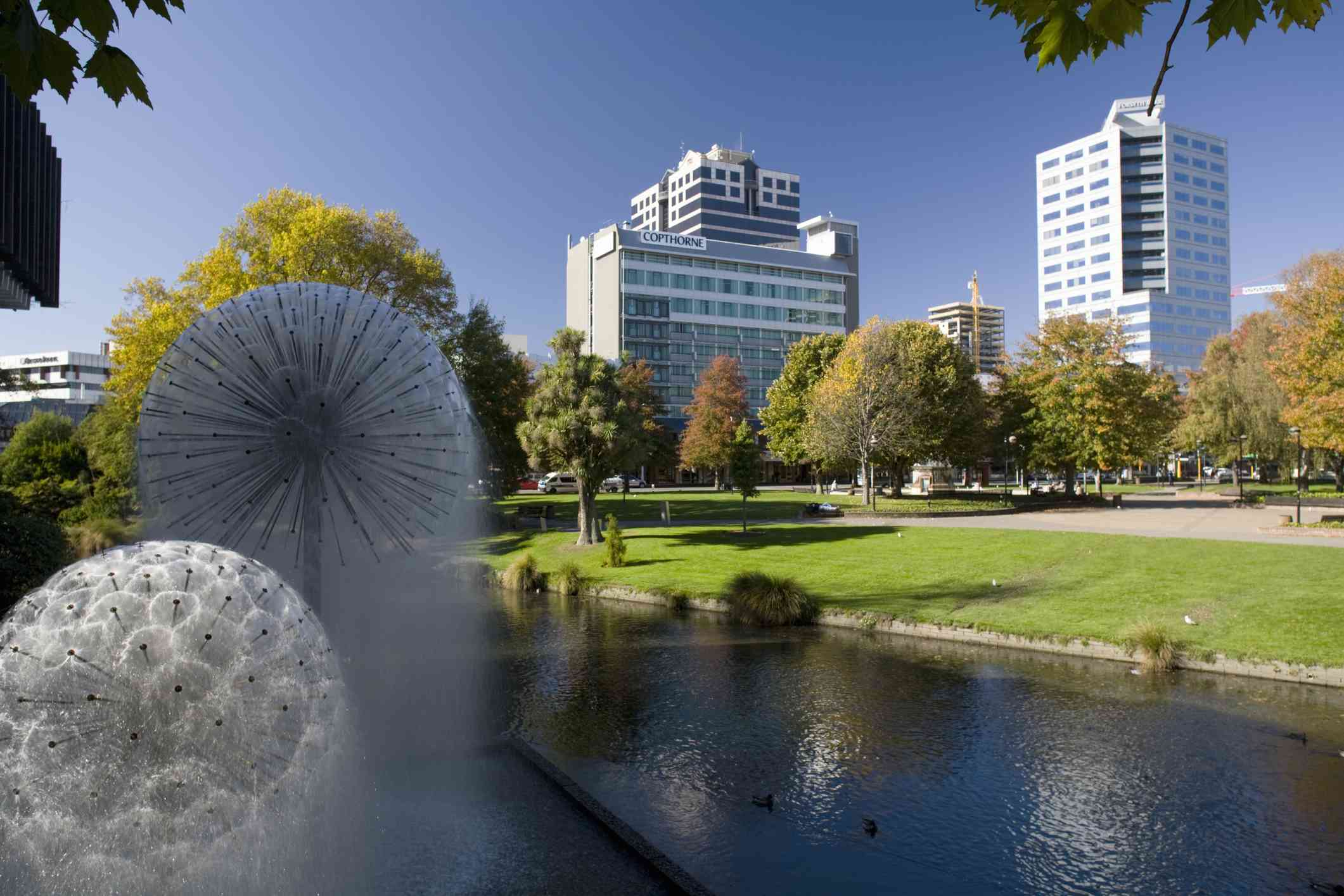 fountains in a riverside park with tall buildings behind