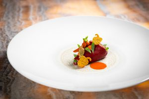 Red amuse bouche on a large white plate