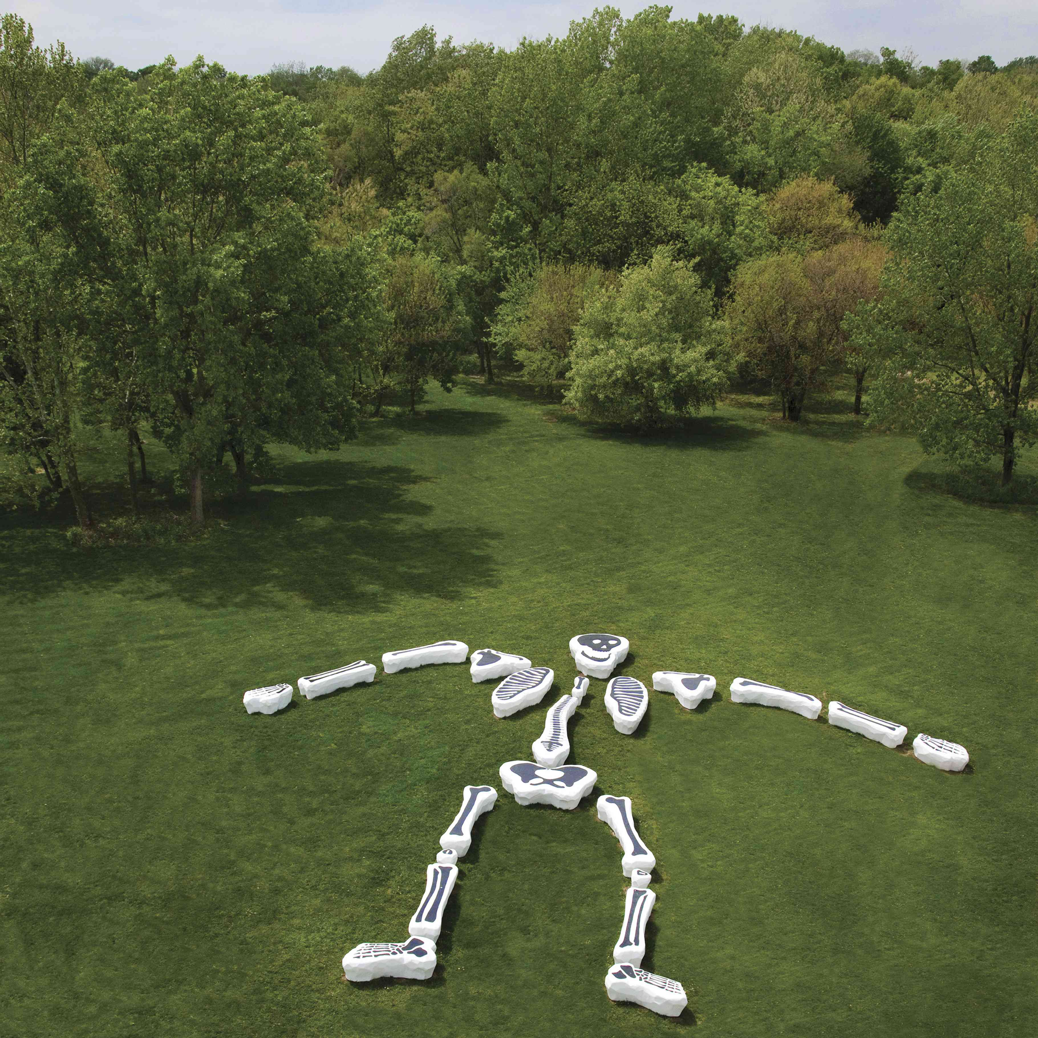 Aerial view of a cartoonish skeleton sculpture composed of painted benches splayed out on a field