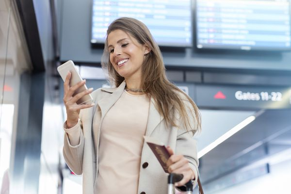 Businesswoman with passport using cell phone in airport
