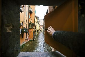 Man opening window and looking at the canal in Bologna, Italy