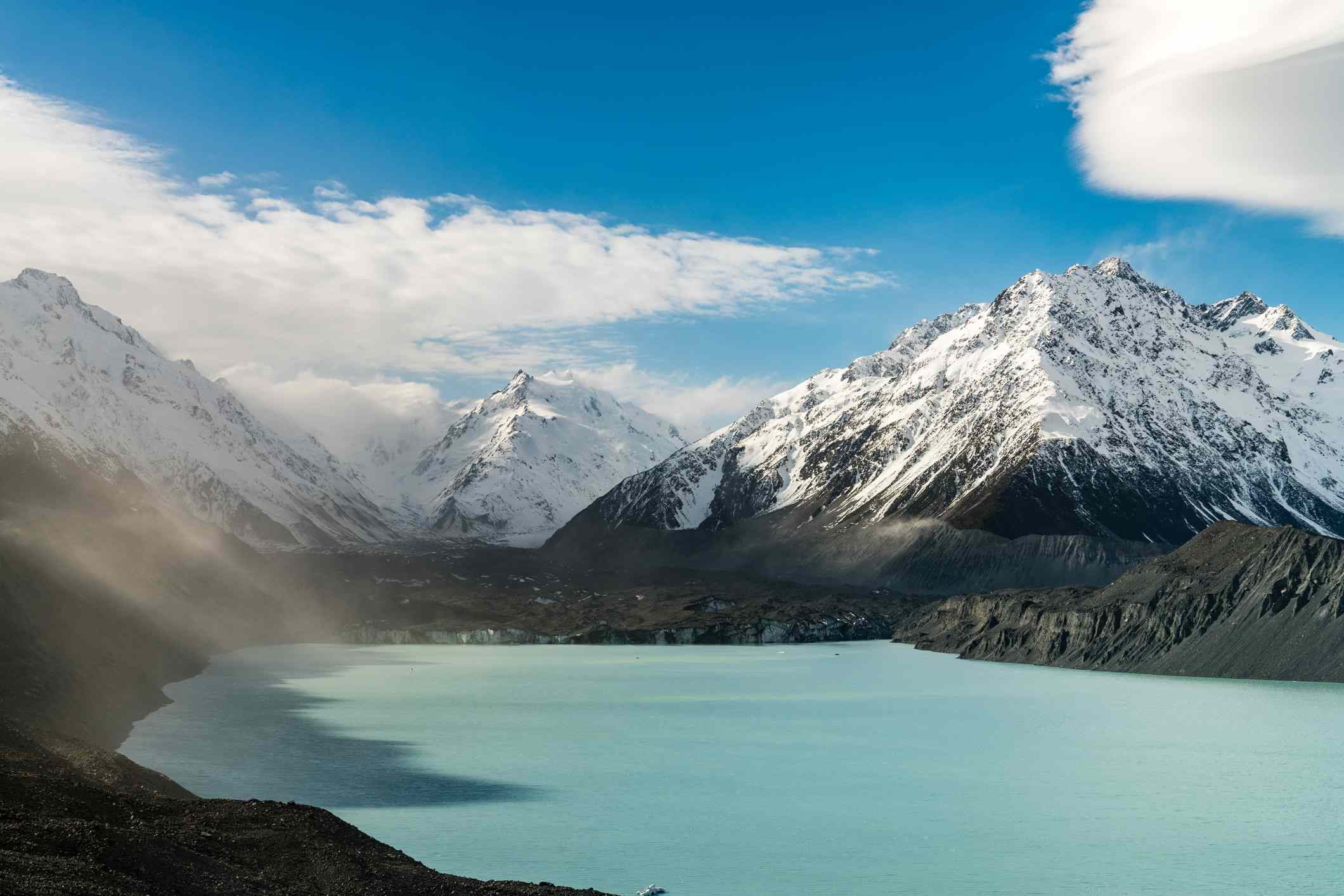 pale blue glacier lake surrounded by snowy mountains with mist in mid-ground