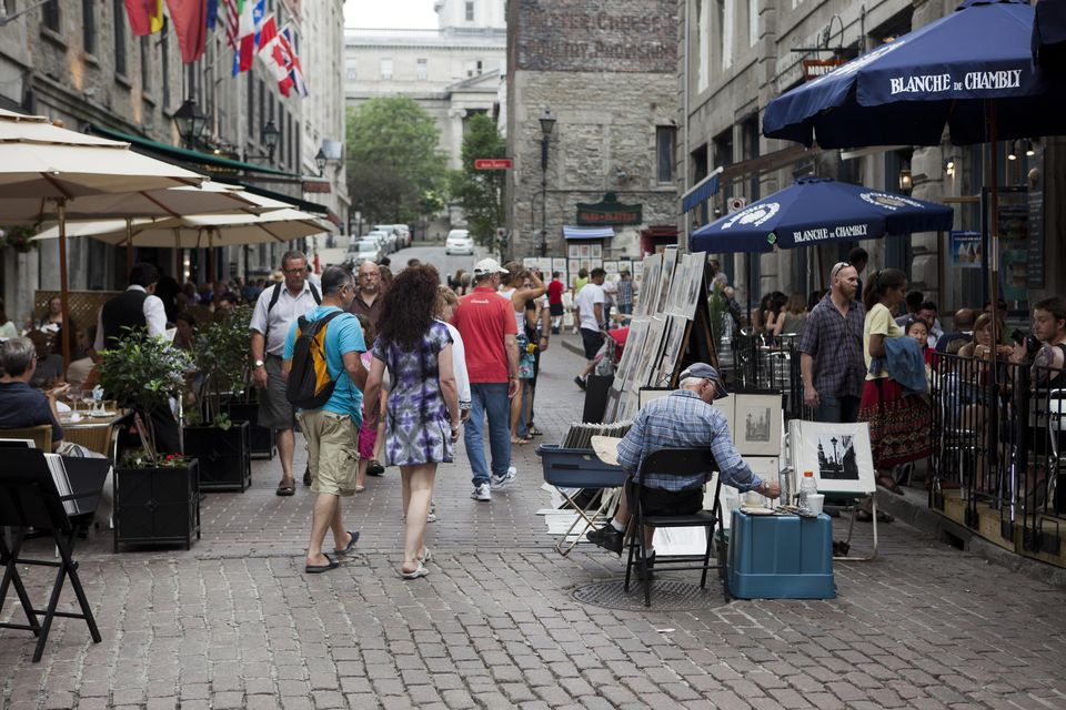 An artist has set up his stand in the Old Town section of Montreal, Quebec, an area of the city that attracts large crowds of tourists, on Canada Day celebrations on the 1st of July.