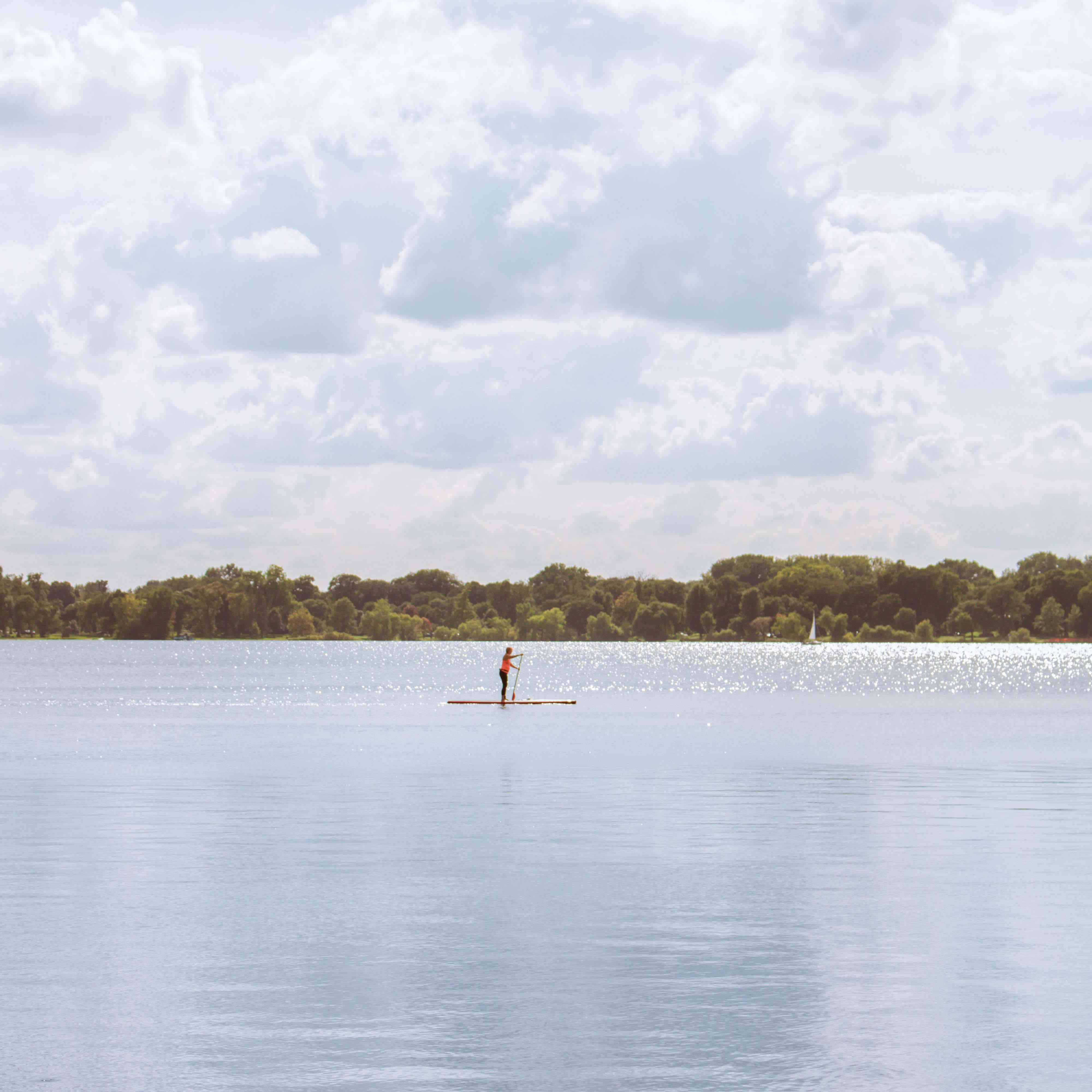 A person paddle boarding through the waters of Lake Calhoun
