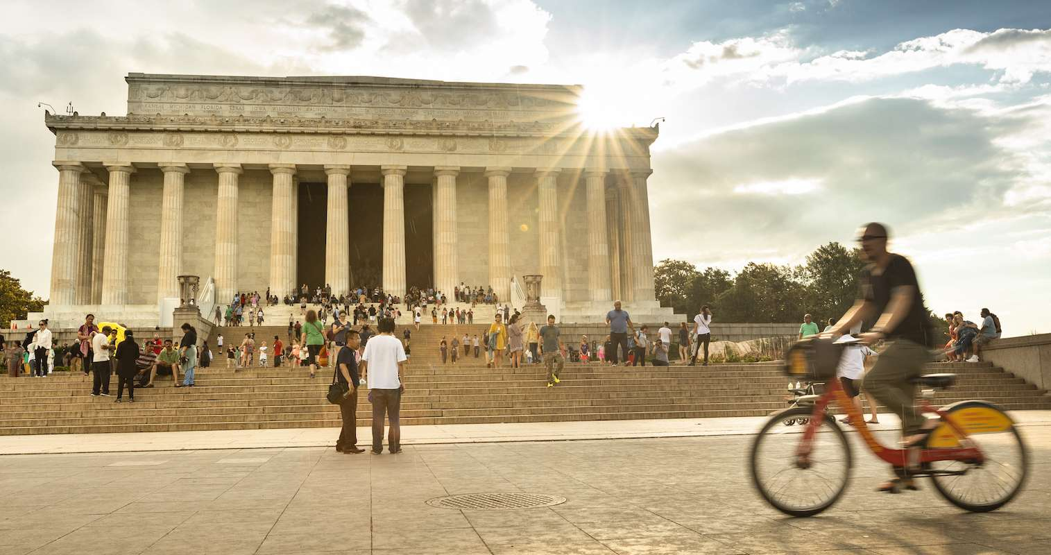 A rider on a bike glides by the Lincoln Monument in Washington, DC