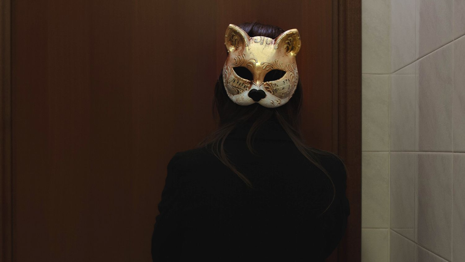 Rear View Of Woman Wearing Mask Against Wall