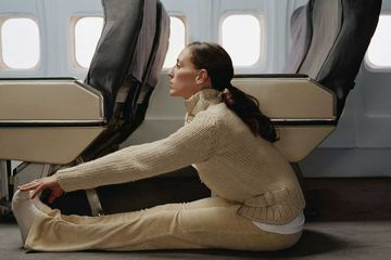 Woman stretching on plane