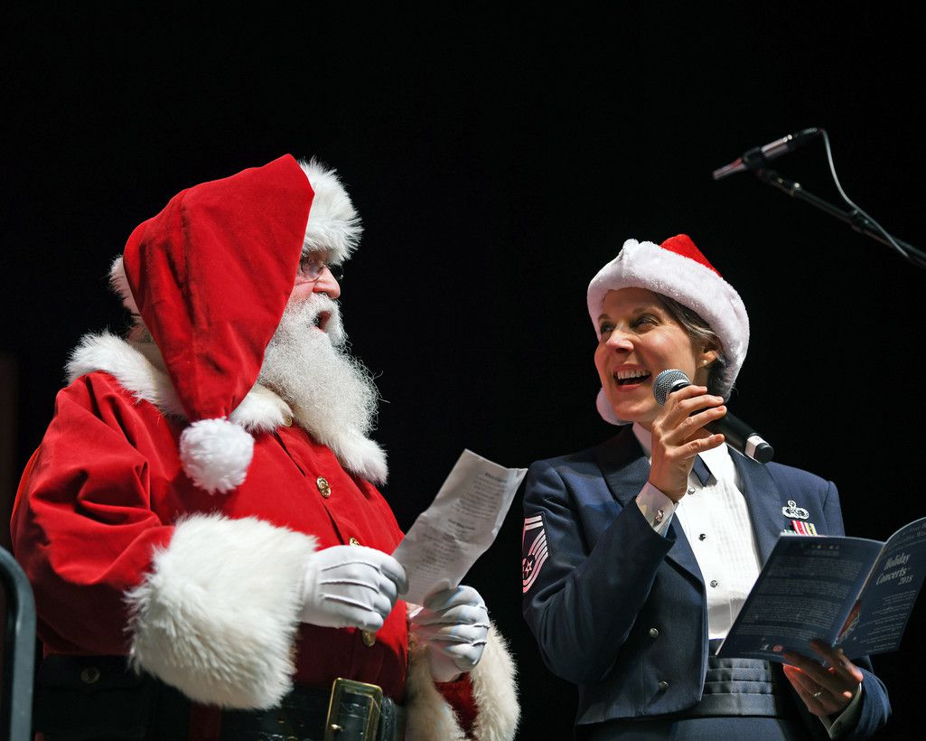 U.S. Air Force Senior Master Sgt. Paula Goetz, a vocalist with the USAF Band of the Golden West from Travis Air Force Base, California, performs with Santa Claus during a performance