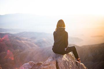 Woman sitting on rock overlooking mountains