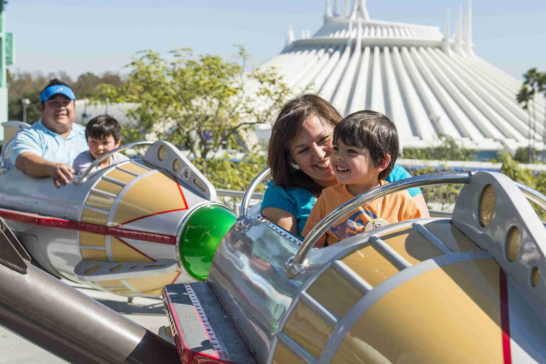 Familia con niños pequeños disfrutando de Astro Orbiter con Space Mountain en el fondo